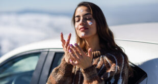 young woman applying sunscreen her face snow landscape